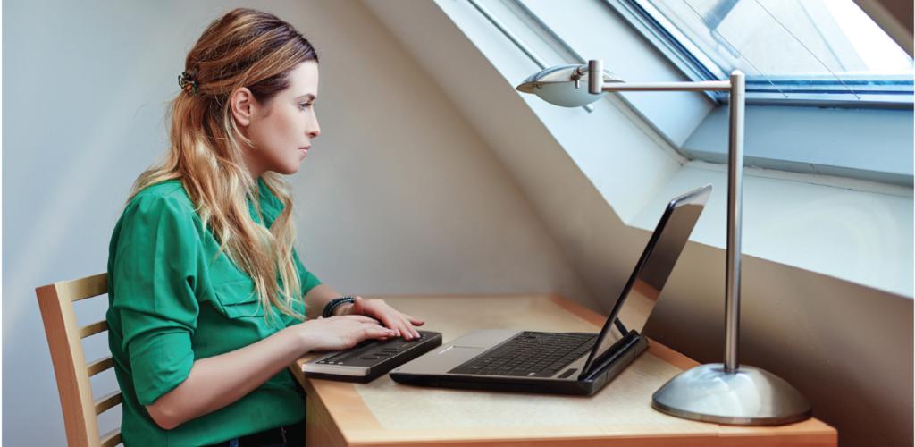 Bilden visar en kvinna som sitter framför en dator med en braille board.